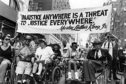 """Black and white photo of several people in the middle of a city street, in wheelchairs. More are coming up behind them and two people are carrying a banner reading """"'Injustice Anywhere Is a Threat to Justice Everywhere' -- Martin Luther King, Jr."""""""